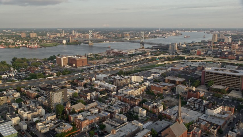 5K stock footage aerial video of Benjamin Franklin Bridge and Delaware River seen from I-95 in North Philadelphia, Pennsylvania, Sunset Aerial Stock Footage | AX80_072
