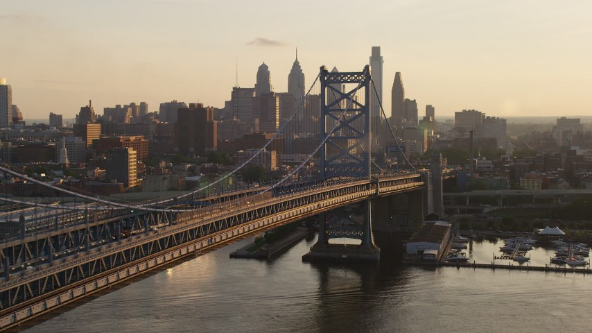 Approach Benjamin Franklin Bridge and the Downtown Philadelphia skyline, Pennsylvania Sunset Aerial Stock Footage | AX80_076