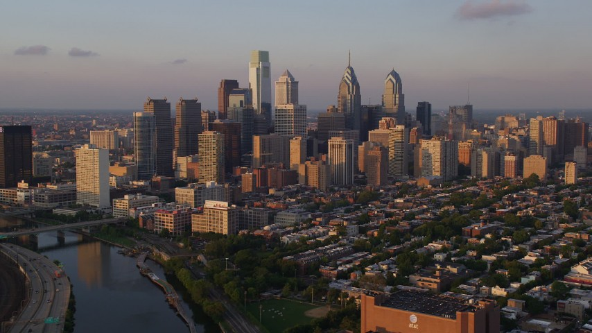 5K aerial video of Downtown Philadelphia skyscrapers and urban neighborhoods in Pennsylvania, Sunset Aerial Stock Footage | AX80_092