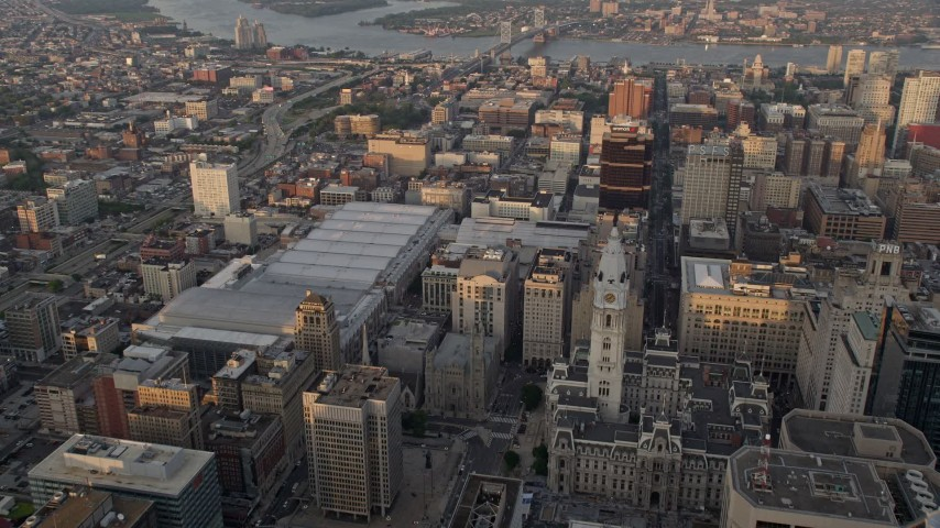 5K stock footage aerial video flying over Downtown Philadelphia skyscrapers, to reveal Convention Center, City Hall in Pennsylvania, Sunset Aerial Stock Footage | AX80_095