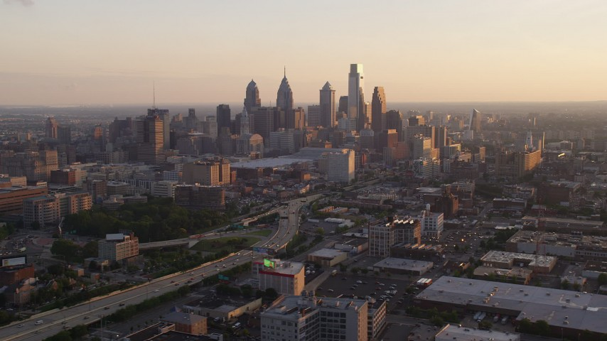 5K stock footage aerial video of Downtown Philadelphia skyscrapers behind the I-676 freeway, Pennsylvania, Sunset Aerial Stock Footage | AX80_098