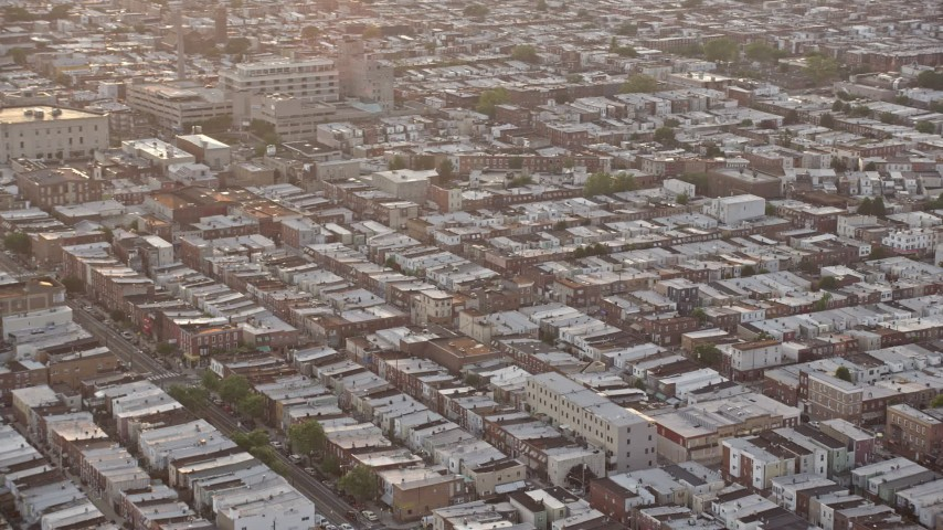 5K stock footage aerial video flying by an urban neighborhood in South Philadelphia and tilt to the busy street, Pennsylvania, Sunset Aerial Stock Footage | AX80_111