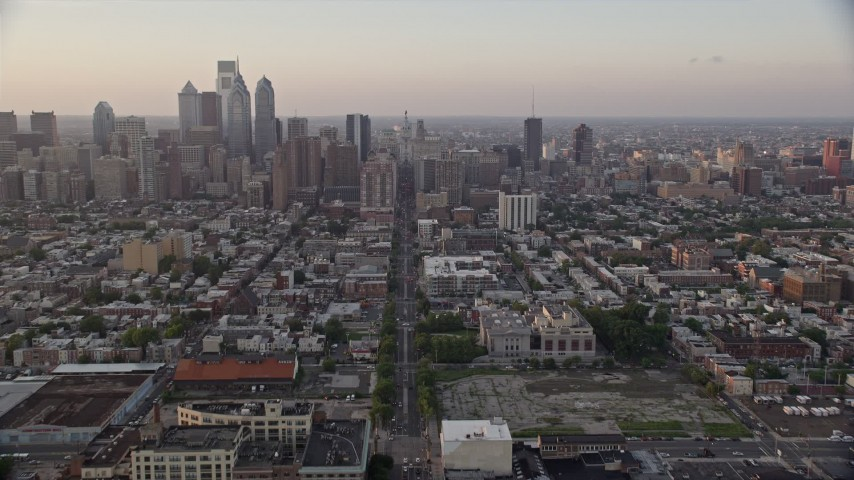 5K stock footage aerial video tilting from Broad Street and urban South Philly neighborhood to reveal and approach Downtown Philadelphia skyline, Pennsylvania, Sunset Aerial Stock Footage | AX80_112E