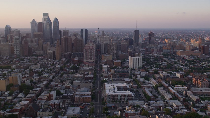 5K stock footage aerial video following Broad Street toward Philadelphia City Hall, Downtown Philadelphia, Pennsylvania, Sunset Aerial Stock Footage | AX80_113