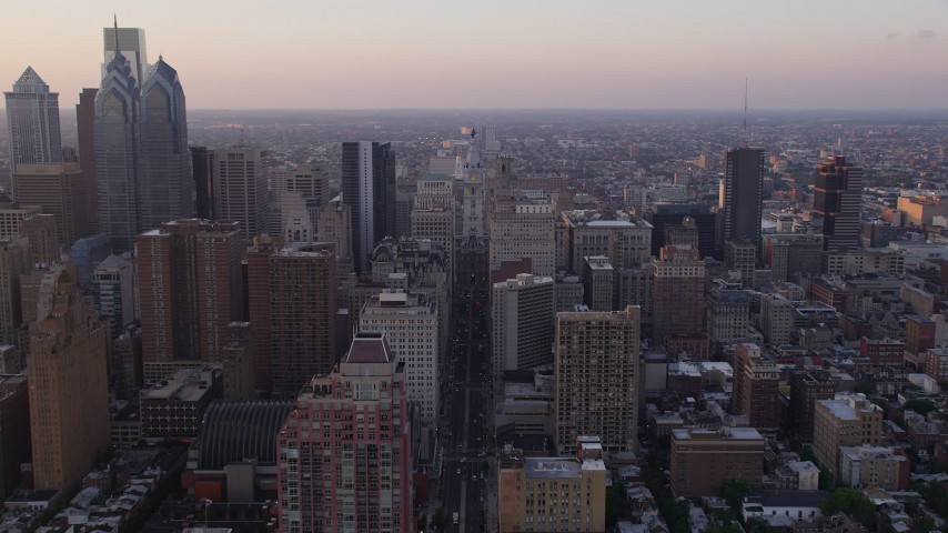 5K stock footage aerial video following Broad Street to approach Philadelphia City Hall, Downtown Philadelphia, Pennsylvania, Sunset Aerial Stock Footage | AX80_114
