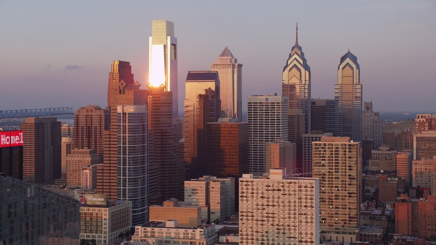 5K stock footage aerial video of sunlight shining off of Downtown Philadelphia skyscrapers, Pennsylvania, Sunset Aerial Stock Footage | AX80_126