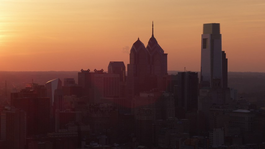 5K aerial video of the setting sun behind the Downtown Philadelphia skyline, Pennsylvania, Sunset Aerial Stock Footage | AX80_130