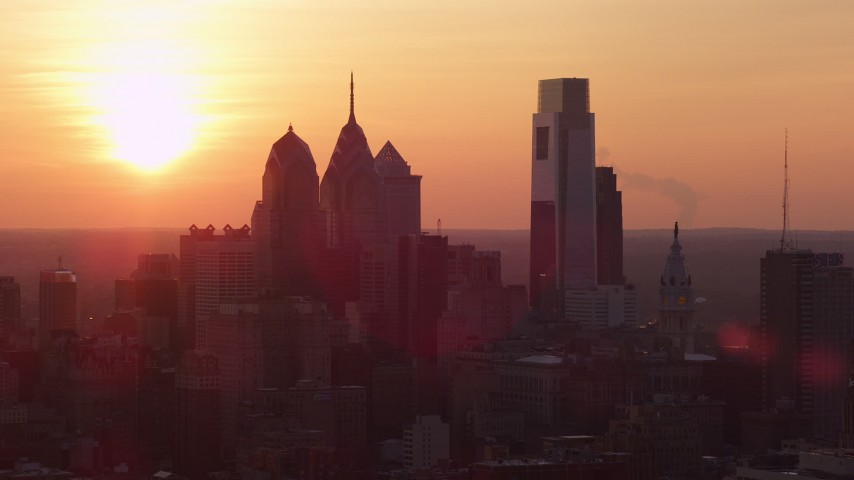 5K stock footage aerial video of Downtown Philadelphia skyline with the setting sun in the background, Pennsylvania, Sunset Aerial Stock Footage | AX80_131