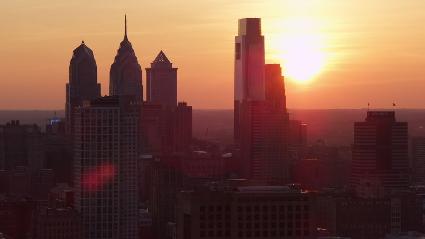 5K stock footage aerial video of the setting sun behind the Downtown Philadelphia skyline, Pennsylvania, Sunset Aerial Stock Footage | AX80_132