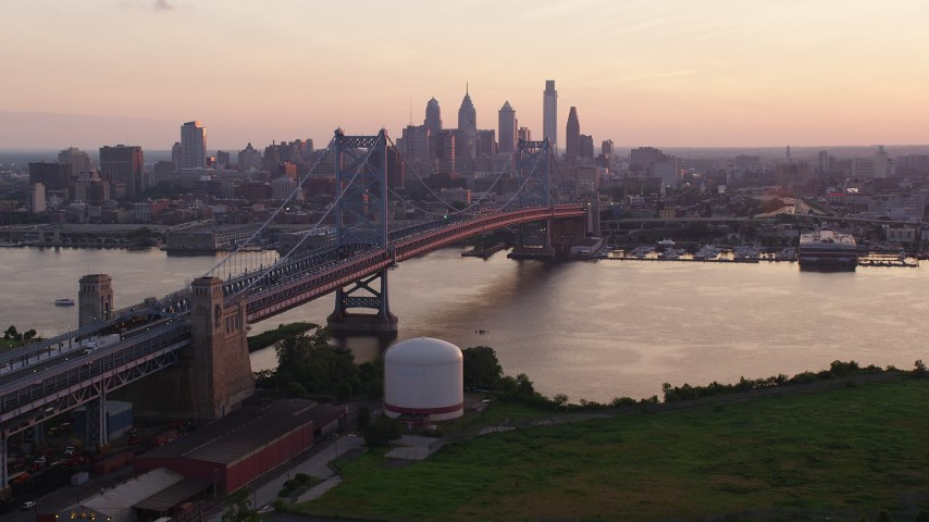 5K stock footage aerial video approaching the Benjamin Franklin Bridge over Delaware River, Downtown Philadelphia skyline, Pennsylvania, Sunset Aerial Stock Footage | AX80_136