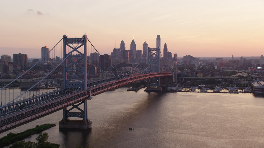 5K stock footage aerial video flying by Benjamin Franklin Bridge toward Downtown Philadelphia skyline, Pennsylvania, Sunset Aerial Stock Footage | AX80_137