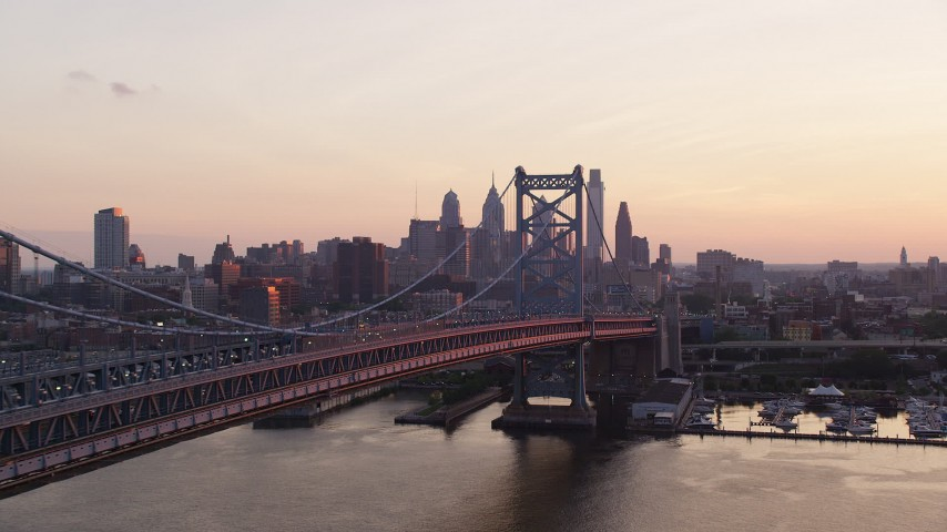 5K stock footage aerial video flying by the Benjamin Franklin Bridge, Downtown Philadelphia skyline in the background, Pennsylvania, Sunset Aerial Stock Footage | AX80_138