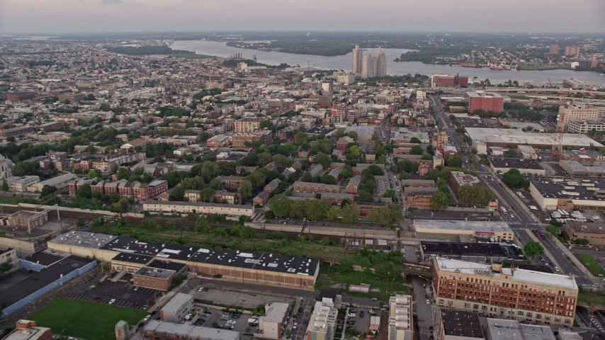 5K stock footage aerial video of row houses by railroad tracks and Edgar Allan Poe House in North Philadelphia, Pennsylvania, Sunset Aerial Stock Footage | AX80_145