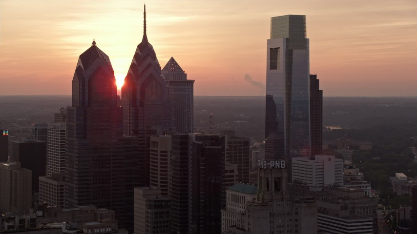 5K stock footage aerial video of tall Downtown Philadelphia skyscrapers and City Hall, reveal setting sun, Pennsylvania, Sunset Aerial Stock Footage | AX80_146E