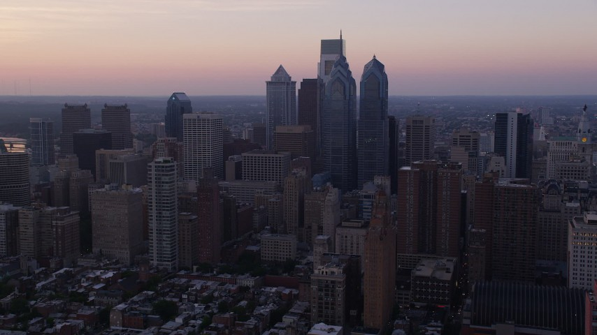 5K aerial video flying by Downtown Philadelphia skyscrapers, Pennsylvania, Sunset Aerial Stock Footage | AX80_150