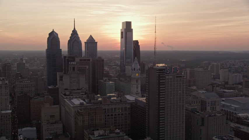 5K stock footage aerial video flying by Downtown Philadelphia skyscrapers to reveal setting sun, Pennsylvania Aerial Stock Footage | AX80_150E