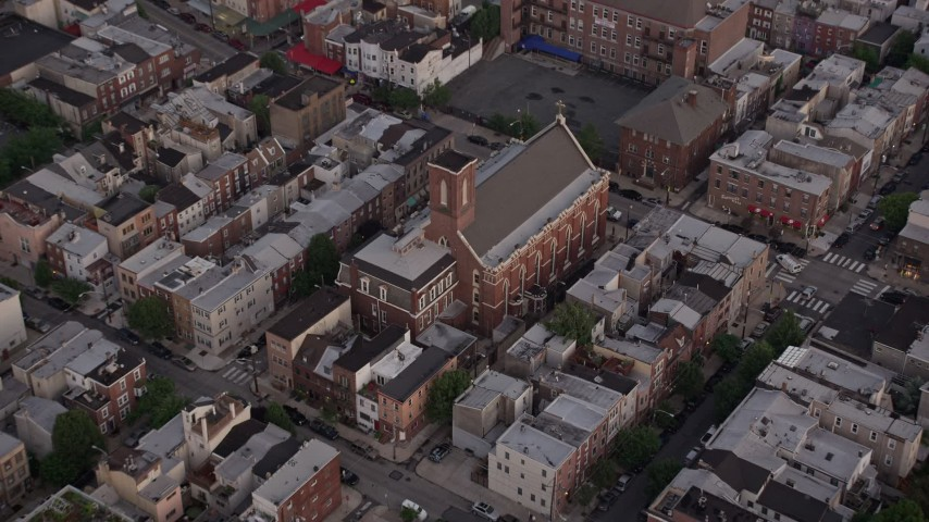 5K stock footage aerial video of Saint Paul Church in an urban neighborhood, South Philadelphia, Pennsylvania, Sunset Aerial Stock Footage | AX80_158
