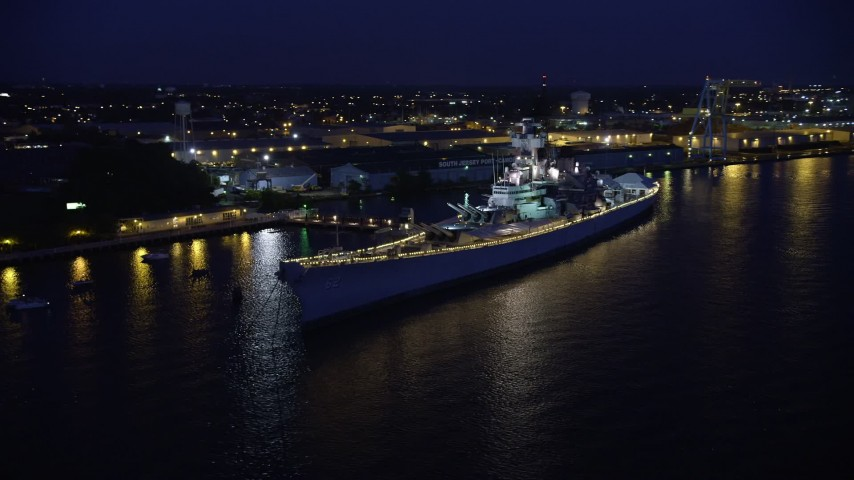 5K stock footage aerial video approaching USS New Jersey battleship on the Delaware River, Camden, New Jersey, Night Aerial Stock Footage | AX81_001