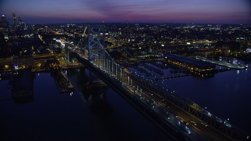 5K aerial video flying by Benjamin Franklin Bridge, reveal Downtown Philadelphia skyline, Pennsylvania, Night Aerial Stock Footage | AX81_004