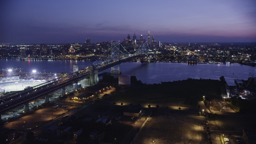 5K aerial video approaching Benjamin Franklin Bridge, Delaware River, and Downtown Philadelphia skyline, Pennsylvania, Night Aerial Stock Footage AX81_007
