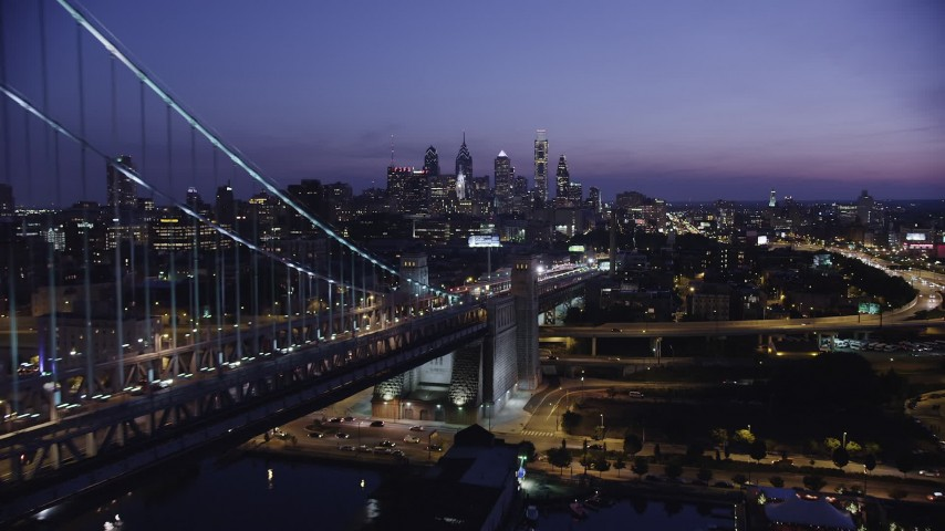 5K stock footage aerial video flying by the Benjamin Franklin Bridge and approach Downtown Philadelphia skyline, Pennsylvania, Night Aerial Stock Footage | AX81_009
