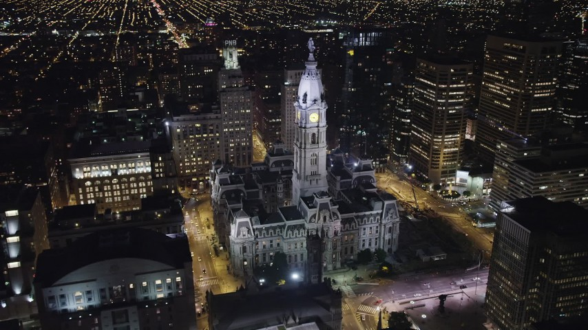 Track Philadelphia City Hall to reveal Downtown Philadelphia skyscrapers, Pennsylvania, Night Aerial Stock Footage AX81_040
