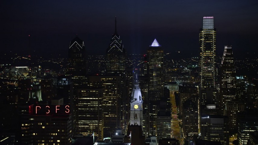 5K stock footage aerial video flying by City Hall clock tower with tall Downtown Philadelphia skyscrapers behind it, Pennsylvania, Night Aerial Stock Footage | AX81_042