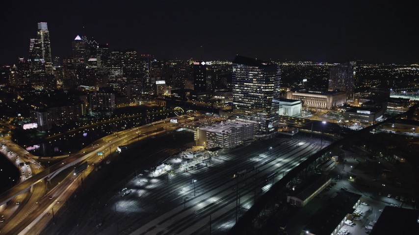 5K stock footage aerial video of Cira Centre by train yard, I-76, and Schuylkill River, across from Downtown Philadelphia skyscrapers, Pennsylvania, Night Aerial Stock Footage | AX81_051