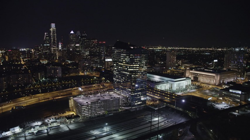 5K stock footage aerial video flying by Cira Centre and 30th Street Station with a view of the Downtown Philadelphia skyscrapers, Pennsylvania at night Aerial Stock Footage | AX81_052