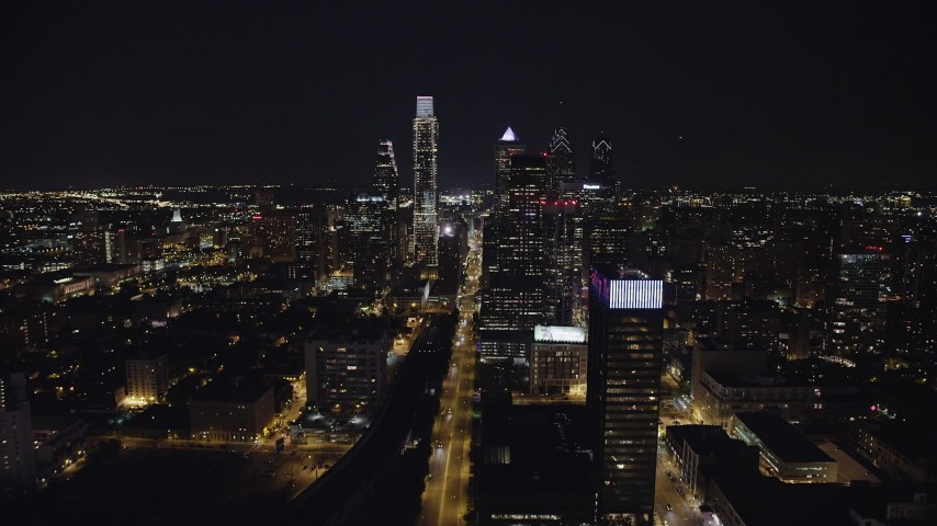 5K stock footage aerial video following John F Kennedy Boulevard to approach Downtown Philadelphia skyscrapers, Pennsylvania, Night Aerial Stock Footage | AX81_053