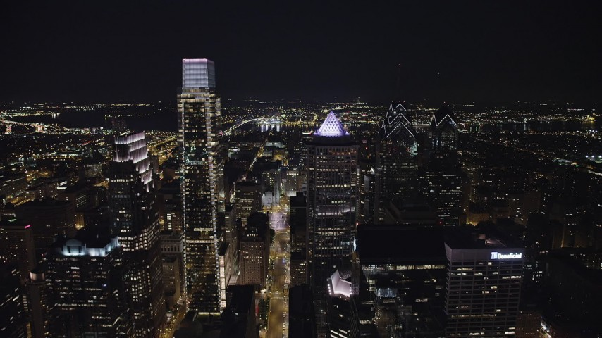 5K stock footage aerial video following John F Kennedy Boulevard and fly over Downtown Philadelphia skyscrapers to reveal City Hall, Pennsylvania, Night Aerial Stock Footage | AX81_054