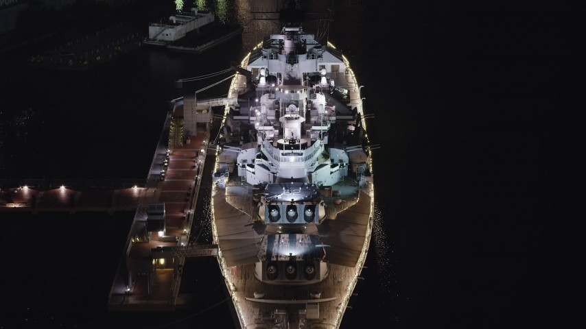 5K aerial video tilting to a bird's eye view of the USS New Jersey, Camden, New Jersey, Night Aerial Stock Footage | AX81_084