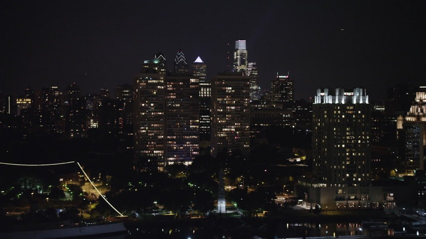 5K stock footage aerial video of Downtown Philadelphia skyline and apartment complexes seen from the historic ship Moshulu, Pennsylvania, Night Aerial Stock Footage | AX81_092