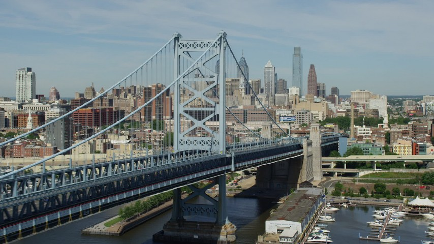 Flyby the Benjamin Franklin Bridge to approach Downtown Philadelphia skyline, Pennsylvania Aerial Stock Footage | AX82_004