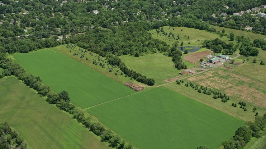 5K stock footage aerial video flying over farm fields and small town neighborhood in Somerset, New Jersey Aerial Stock Footage | AX83_044
