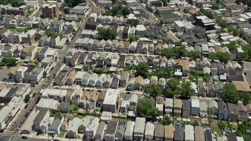 5K stock footage aerial video tilting from urban Newark homes to reveal and approach Manhattan skyline in the background, New Jersey & New York Aerial Stock Footage   AX83_097