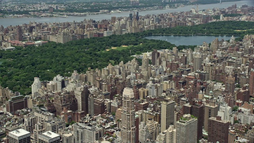 5K stock footage aerial video flying over Upper East Side apartment buildings to approach Central Park, New York City Aerial Stock Footage AX83_132 | Axiom Images
