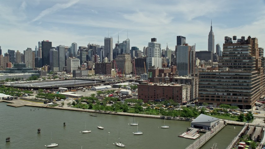 5K stock footage aerial video flying by Starrett-Lehigh Building and Hudson Yards, land at heliport, with a view of Midtown Manhattan skyscrapers, New York City Aerial Stock Footage | AX83_151E