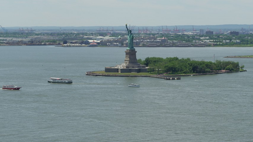 5K stock footage aerial video of Statue of Liberty and passing ferries in New York Harbor, New York City Aerial Stock Footage | AX83_191