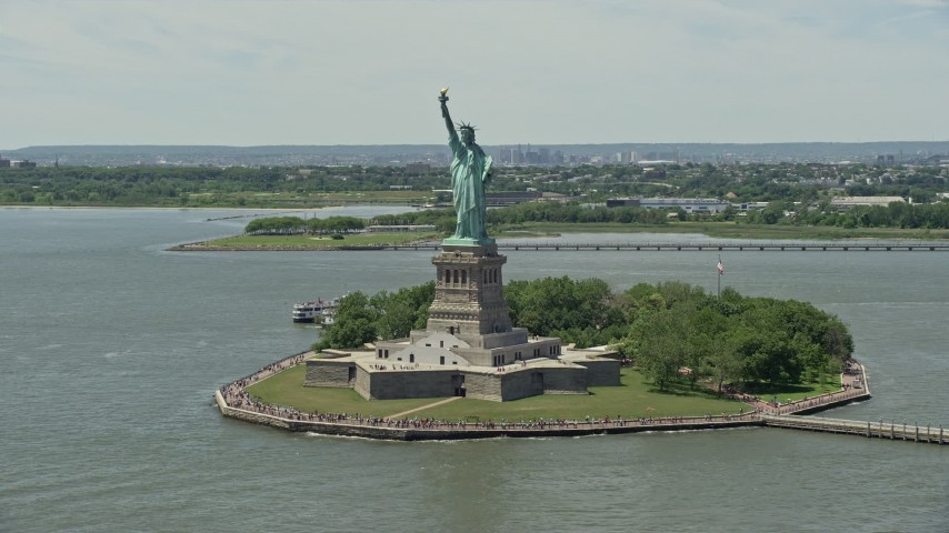 5K stock footage aerial video flying by Statue of Liberty with tourists in New York Harbor, New York City Aerial Stock Footage | AX83_193