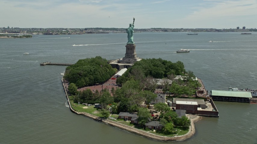 5K aerial video orbiting Statue of Liberty with a view of New York Harbor, New York Aerial Stock Footage | AX83_197