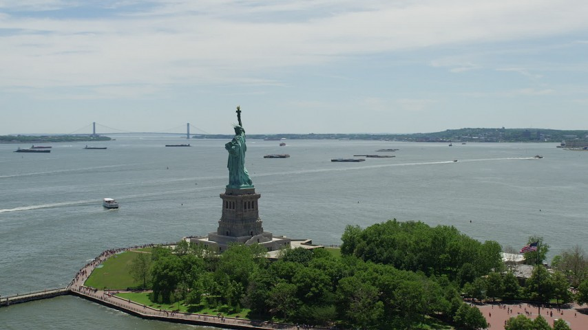 5K stock footage aerial video zooming in on Statue of Liberty overlooking New York Harbor, New York Aerial Stock Footage | AX83_198