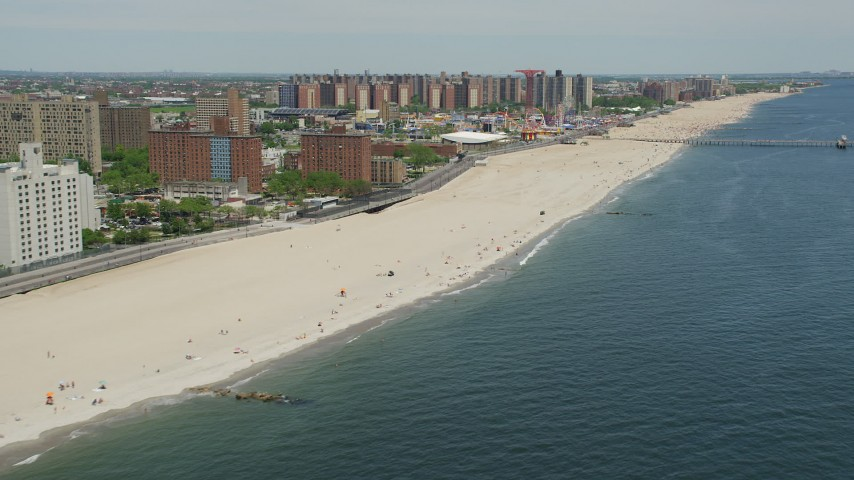 5K stock footage aerial video flying over beach goers on Coney Island Beach to approach Luna Park, Brooklyn, New York City Aerial Stock Footage | AX83_212