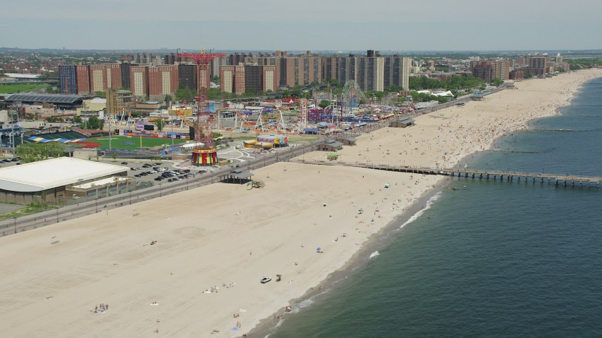 5K stock footage aerial video flying by sunbathers on the beach and rides at Luna Park, Coney Island, Brooklyn, New York City Aerial Stock Footage | AX83_213
