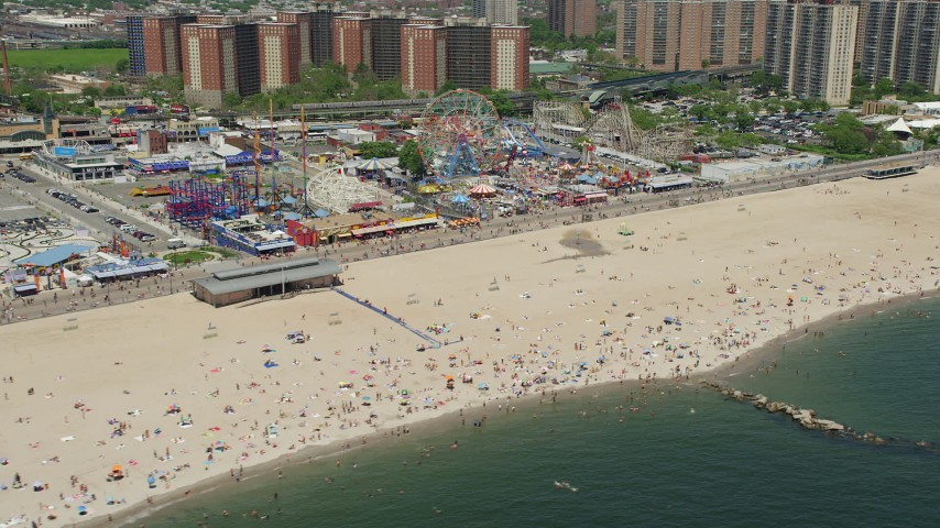 5K stock footage aerial video of sunbathers at Coney Island Beach by Luna Park, Brooklyn, New York City Aerial Stock Footage | AX83_214