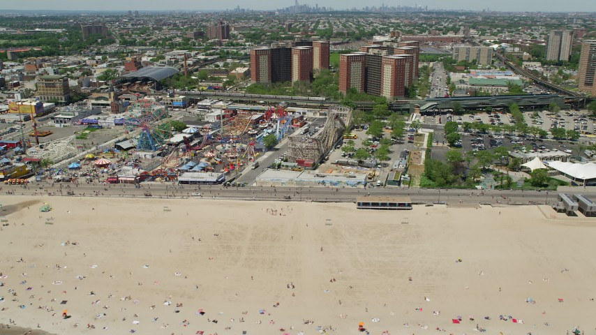5K stock footage aerial video orbiting Luna Park and the boardwalk beside Coney Island Beach, Brooklyn, New York City Aerial Stock Footage | AX83_215