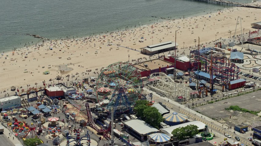 5K stock footage aerial video of the Ferris wheel at Luna Park and beach goers on Coney Island Beach, Brooklyn, New York City Aerial Stock Footage | AX83_217