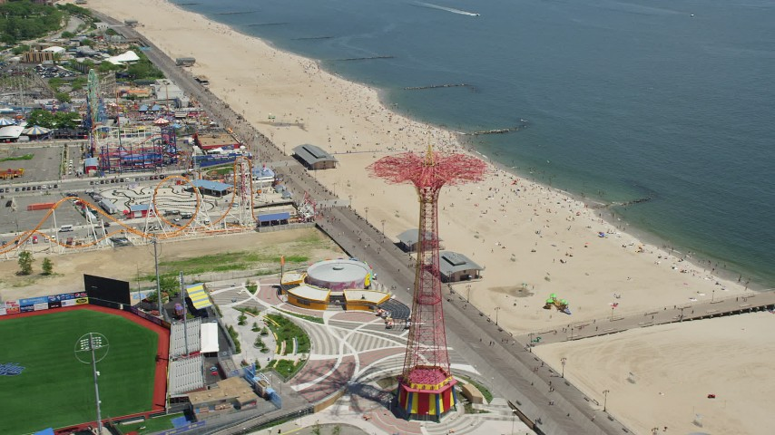 5K stock footage aerial video flying by Luna Park, Riegelmann Boardwalk, and Coney Island Beach sunbathers, Brooklyn, New York City Aerial Stock Footage | AX83_220