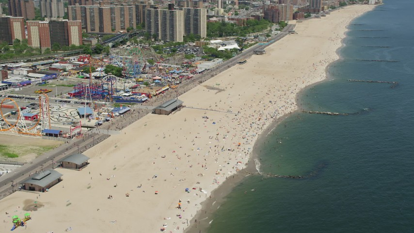 5K stock footage aerial video orbiting Luna Park rides and Coney Island Beach, Brooklyn, New York City Aerial Stock Footage | AX83_221