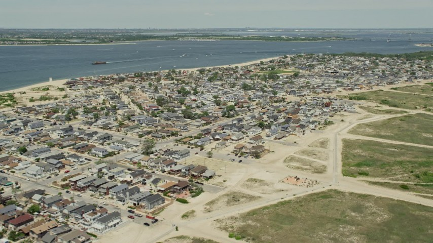5K stock footage aerial video flying by residential neighborhoods near the water, Breezy Point, Queens, New York Aerial Stock Footage | AX83_224